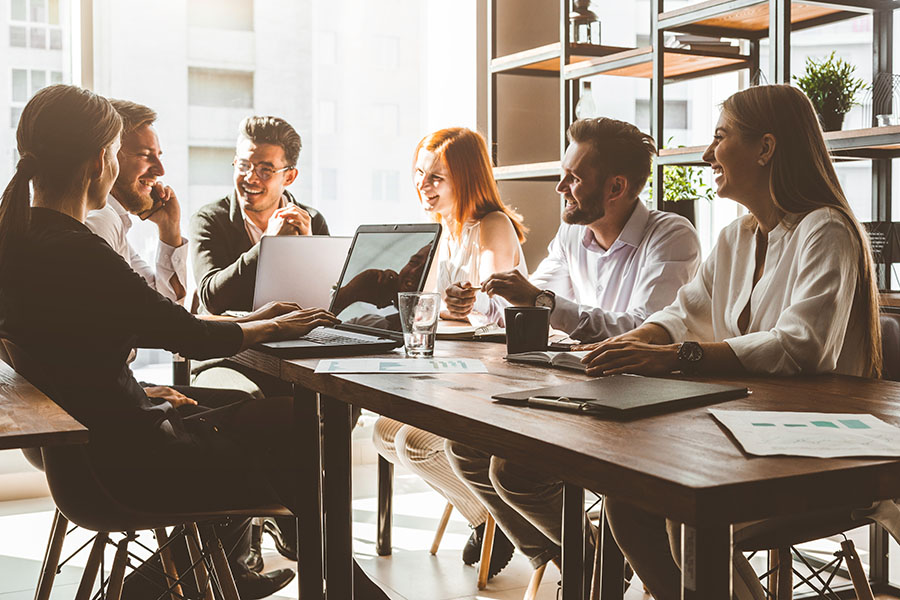 Employee Benefits - Group of Happy Employees Sitting Around Table in Office During Meeting