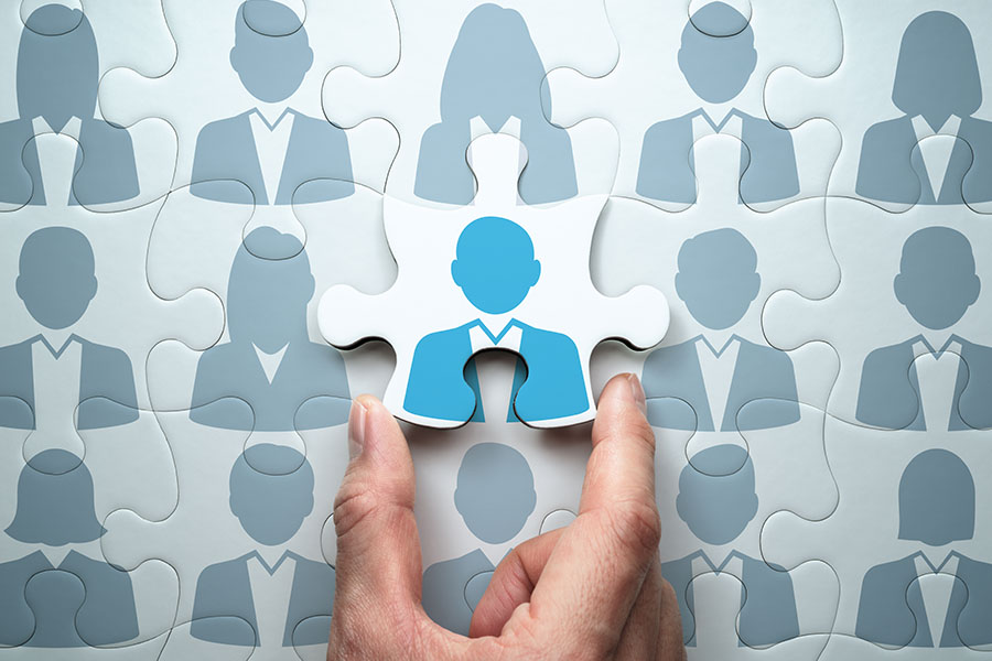 Human Resource Information Systems - Human Resources Concept with a Man Holding a Puzzle Piece of an Employee